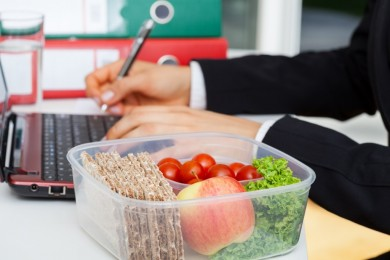 Box with healthy food placed on the office desk